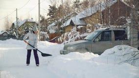 Η νέα γυναίκα καθαρίζει το χιόνι από το φτυάρι για το αυτοκίνητο στα προάστια το χειμώνα φιλμ μικρού μήκους