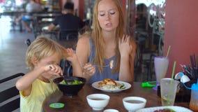 Η νέα γυναίκα και ο γιος της τρώνε τα κινεζικά τρόφιμα σε έναν καφέ οδών απόθεμα βίντεο