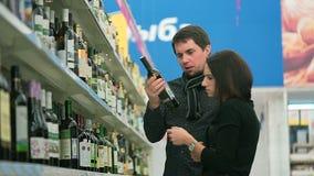 Η νέα γυναίκα και ο φίλος της επιλέγουν ένα μπουκάλι του κρασιού φιλμ μικρού μήκους