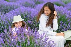 Η νέα γυναίκα και το κορίτσι είναι στο lavender τομέα, όμορφο θερινό τοπίο με τα κόκκινα λουλούδια παπαρουνών στοκ φωτογραφία