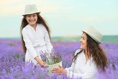 Η νέα γυναίκα και το κορίτσι είναι στο lavender τομέα, όμορφο θερινό τοπίο με τα κόκκινα λουλούδια παπαρουνών Στοκ φωτογραφία με δικαίωμα ελεύθερης χρήσης
