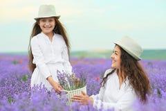 Η νέα γυναίκα και το κορίτσι είναι στο lavender τομέα, όμορφο θερινό τοπίο με τα κόκκινα λουλούδια παπαρουνών Στοκ Φωτογραφίες