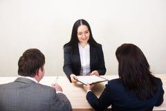 Η νέα γυναίκα κατά τη διάρκεια της συνέντευξης εργασίας και τα μέλη Στοκ φωτογραφία με δικαίωμα ελεύθερης χρήσης
