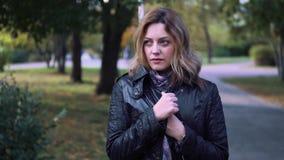 Η νέα γυναίκα κατέψυξε και τυλίχτηκε σε ένα μαντίλι παγωμένο κορίτσι στο πάρκο φθινοπώρου απόθεμα βίντεο