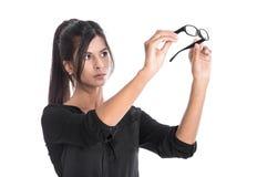 Η νέα γυναίκα κοιτάζει μέσω των γυαλιών τους - απομονωμένη επιχείρηση Στοκ Φωτογραφία