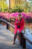 Η νέα γυναίκα κοιτάζει σε ένα smartphone και χαμογελά Στοκ φωτογραφίες με δικαίωμα ελεύθερης χρήσης