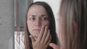 Η νέα γυναίκα κοιτάζει στα σπυράκια της στο δέρμα προσώπου στον καθρέφτη απόθεμα βίντεο