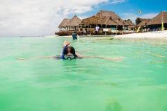 Η νέα γυναίκα κολυμπά με την κολύμβηση με αναπνευστήρα τη μάσκα στον τυρκουάζ ωκεανό στοκ εικόνα