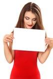 Η νέα γυναίκα κρατά ένα καθαρό φύλλο του εγγράφου διαθέσιμο στοκ φωτογραφίες
