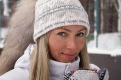 Η νέα γυναίκα κρατά στο χέρι της ένα φλυτζάνι των thermos ΚΑΠ τσαγιού υπαίθρια μια παγωμένη ημέρα στοκ φωτογραφία
