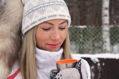 Η νέα γυναίκα κρατά στο χέρι της ένα φλυτζάνι των thermos ΚΑΠ τσαγιού υπαίθρια μια παγωμένη ημέρα στοκ φωτογραφία με δικαίωμα ελεύθερης χρήσης