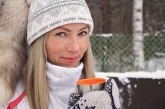 Η νέα γυναίκα κρατά στο χέρι της ένα φλυτζάνι των thermos ΚΑΠ τσαγιού υπαίθρια μια παγωμένη ημέρα στοκ εικόνα