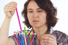 Η νέα γυναίκα κρατά τα μολύβια χρώματος Στοκ Φωτογραφίες