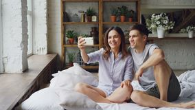 Η νέα γυναίκα κρατά το smartphone, σχετικά με την οθόνη και κάνει την τηλεοπτική κλήση μαζί με το σύζυγό της καθμένος στο κρεβάτι φιλμ μικρού μήκους