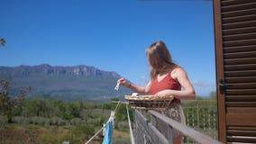Η νέα γυναίκα κρεμά τα πλυμένα ενδύματα στο μπαλκόνι, συνδέει clothespins στοκ εικόνα