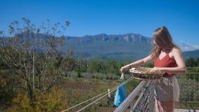 Η νέα γυναίκα κρεμά το πλυντήριο στο μπαλκόνι, συνδέει clothespins στοκ φωτογραφία με δικαίωμα ελεύθερης χρήσης
