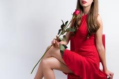 Η νέα γυναίκα με ένα κόκκινο φόρεμα και αυξήθηκε Στοκ Εικόνες