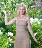 Η νέα γυναίκα με δαπάνες μιας τις μακροχρόνιες δίκαιες τρίχας ενάντια σε έναν κήπο Apple-δέντρων Στοκ Εικόνες