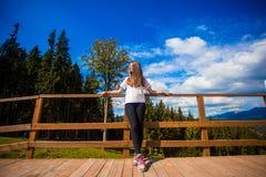 Η νέα γυναίκα με μακρυμάλλη στο φράκτη του πεζουλιού απολαμβάνει την όμορφη θέα των βουνών στοκ εικόνα