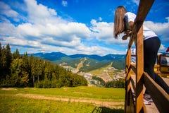 Η νέα γυναίκα με μακρυμάλλη στο φράκτη του πεζουλιού απολαμβάνει την όμορφη θέα των βουνών στοκ εικόνα με δικαίωμα ελεύθερης χρήσης