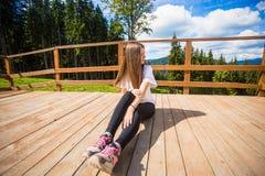 Η νέα γυναίκα με μακρυμάλλη στο φράκτη του πεζουλιού απολαμβάνει την όμορφη θέα των βουνών στοκ φωτογραφίες