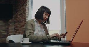 Η νέα γυναίκα με μια κοντή τρίχα έκοψε τη διαταγή κινηματογραφήσεων σε πρώτο πλάνο κάτι από το lap-top χρησιμοποιώντας την κάρτα απόθεμα βίντεο
