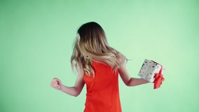Η νέα γυναίκα με τα αστεία γυαλιά και παρόντα διαθέσιμο χορεύει σε ένα πράσινο υπόβαθρο φιλμ μικρού μήκους