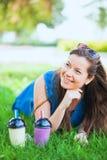 Η νέα γυναίκα με τα γυαλιά ηλίου πίνει τα juicy νόστιμα milkshakes στην πράσινη χλόη χορτοταπήτων στοκ εικόνες