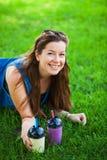 Η νέα γυναίκα με τα γυαλιά ηλίου πίνει τα juicy νόστιμα milkshakes στην πράσινη χλόη χορτοταπήτων στοκ φωτογραφίες