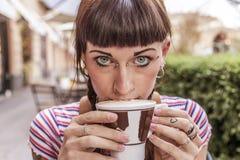 Η νέα γυναίκα με τα μπλε μάτια παίρνει τα χείλια της βρώμικα με την κρέμα στοκ εικόνες