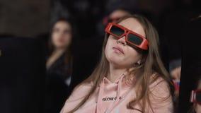 Η νέα γυναίκα με τα τρισδιάστατα γυαλιά προσέχει τον κινηματογράφο στον κινηματογράφο απόθεμα βίντεο