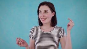 Η νέα γυναίκα με την εξασθένιση ακρόασης ακούει χωρίς ενίσχυση ακρόασης στο μπλε υπόβαθρο απόθεμα βίντεο
