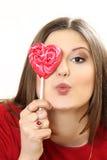 Η νέα γυναίκα με την καρδιά καραμελών ζάχαρης σε ένα ραβδί στοκ φωτογραφία με δικαίωμα ελεύθερης χρήσης