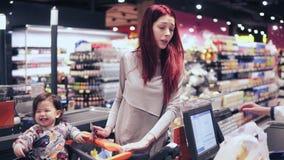 Η νέα γυναίκα με την κόκκινη τρίχα πληρώνει για την αγορά στο μετρητή ελέγχων ενώ ο γιος της είναι γέλιο, καθμένος στις αγορές απόθεμα βίντεο