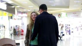 Η νέα γυναίκα με την ταμπλέτα συναντά τον τύπο στη λεωφόρο αγορών απόθεμα βίντεο