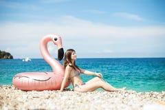 Η νέα γυναίκα με τη συνεδρίαση μπικινιών κοντά στο γίγαντα διόγκωσε το φλαμίγκο σε μια παραλία με το νερό turquois της ιόνιας θάλ στοκ φωτογραφία
