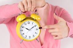 Η νέα γυναίκα με το αναδρομικό παλαιό ξυπνητήρι διαθέσιμο και παρουσιάζει με το δάχτυλο εγκαίρως στοκ φωτογραφία