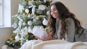 Η νέα γυναίκα με το δώρο στα χέρια βρίσκεται στον καναπέ και εξετάζει τη κάμερα στο πράσινο χριστουγεννιάτικο δέντρο υποβάθρου απόθεμα βίντεο
