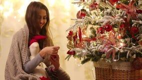 Η νέα γυναίκα με το καρό και Άγιος Βασίλης στα χαμόγελα χεριών της, διακοσμούν τους κλάδους του χριστουγεννιάτικου δέντρου από τα απόθεμα βίντεο