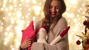 Η νέα γυναίκα με το καρό και Άγιο Βασίλη κρατά το μαξιλάρι στη μορφή αστεριών στα χέρια της και περπατά δίπλα στο χριστουγεννιάτι απόθεμα βίντεο