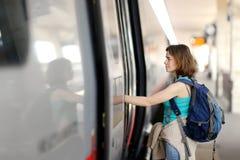 Η νέα γυναίκα με το σακίδιο πλάτης παίρνει το τραίνο στοκ εικόνες με δικαίωμα ελεύθερης χρήσης