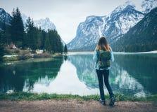 Η νέα γυναίκα με το σακίδιο πλάτης στέκεται στην ακτή της λίμνης στοκ εικόνα