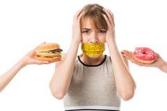 η νέα γυναίκα με το στόμα εσύνδεσε τη μέτρηση της ταινίας κραυγάζοντας ενώ άνθρωποι που δίνουν το άχρηστο φαγητό της Στοκ Εικόνα