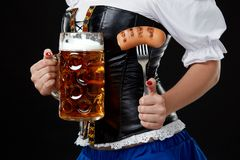 Η νέα γυναίκα με το dirndl κρατά την μπύρα Oktoberfest stein Στη μαύρη ανασκόπηση Στοκ Εικόνες