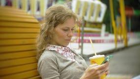 Η νέα γυναίκα με το milkshake και το κύτταρο τηλεφωνούν υπαίθρια σε έναν άνετο δημιουργικό πάγκο απόθεμα βίντεο