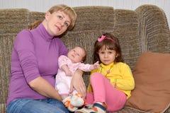 Η νέα γυναίκα με δύο μικρά παιδιά 3 οικογενειακά κορίτσια καναπέδων φωτογραφικών μηχανών που φαίνονται πορτοκαλί πορτρέτο μητέρων Στοκ φωτογραφία με δικαίωμα ελεύθερης χρήσης