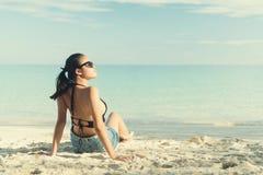 Η νέα γυναίκα μόδας χαλαρώνει στην παραλία Στοκ Φωτογραφίες