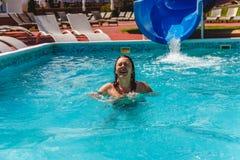 η νέα γυναίκα ξεγλίστρησε το waterslide στη λίμνη και τα γέλια στοκ εικόνες με δικαίωμα ελεύθερης χρήσης