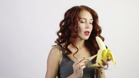 Η νέα γυναίκα ξεφλουδίζει και τρώει την μπανάνα στο άσπρο studi απόθεμα βίντεο