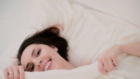 Η νέα γυναίκα ξυπνά και έχει τη διασκέδαση στο κρεβάτι Έναρξη κοριτσιών στο κρύψιμο στο πλαίσιο των φύλλων, την παραγωγή του αστε φιλμ μικρού μήκους